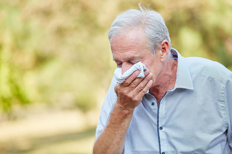 Portrait Of Man Suffering From Cold Virus In Park