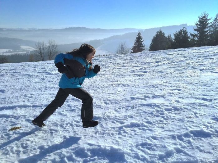 Full length of boy playing in snow