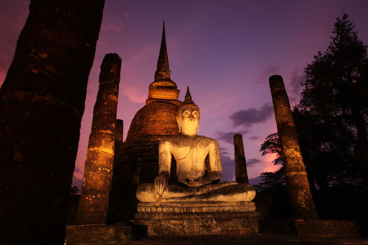 Low angle view of buddha statue and temple against sky at night