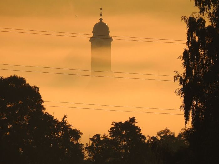 Low angle view of bell tower in foggy weather during sunrise