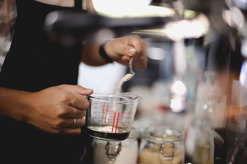 The barista is pouring the coffee mixture.