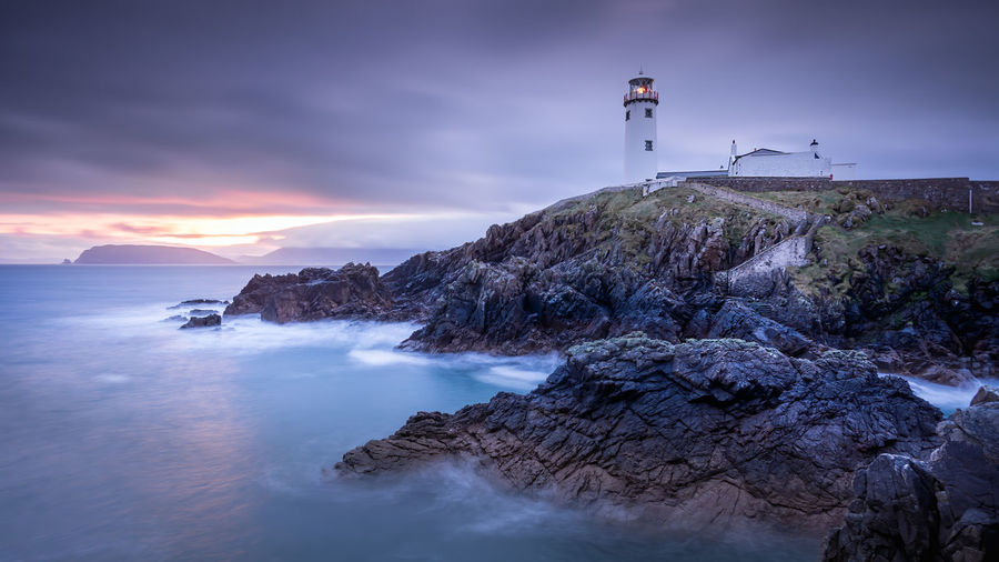 Lighthouse on rocks by sea against sky during sunset