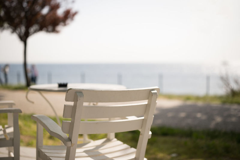 Close-up of empty chairs and table against sea