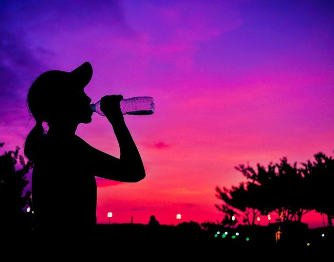 Silhouette woman drinking water from plastic bottle after running in Park with twilight sky. Twilight Healthy Excercise Runner Drinking Silhouette Sky Sunset Pink Color Real People Standing Side View