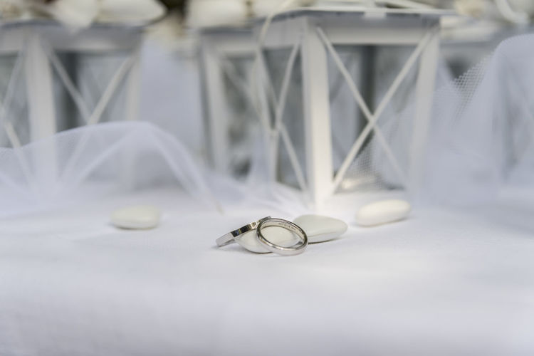 Close up of Wedding rings near comfits and wedding favors Indoors  White No People Colors Texttile Still Life Wedding Close-up Wedding Ring Table Jewelry High Angle View Ring Celebration Event Focus On Foreground Metal Selective Focus
