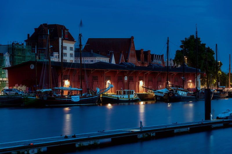 Sailboats moored in river against buildings in city at dusk