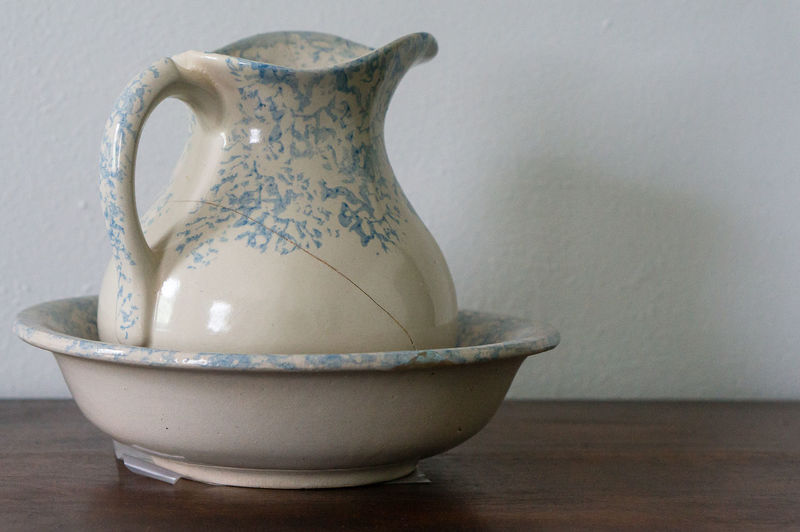 Close-up of cracked porcelain jug in bowl on table