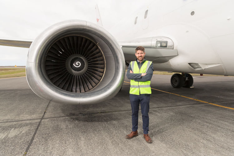Portrait of man standing against airplane