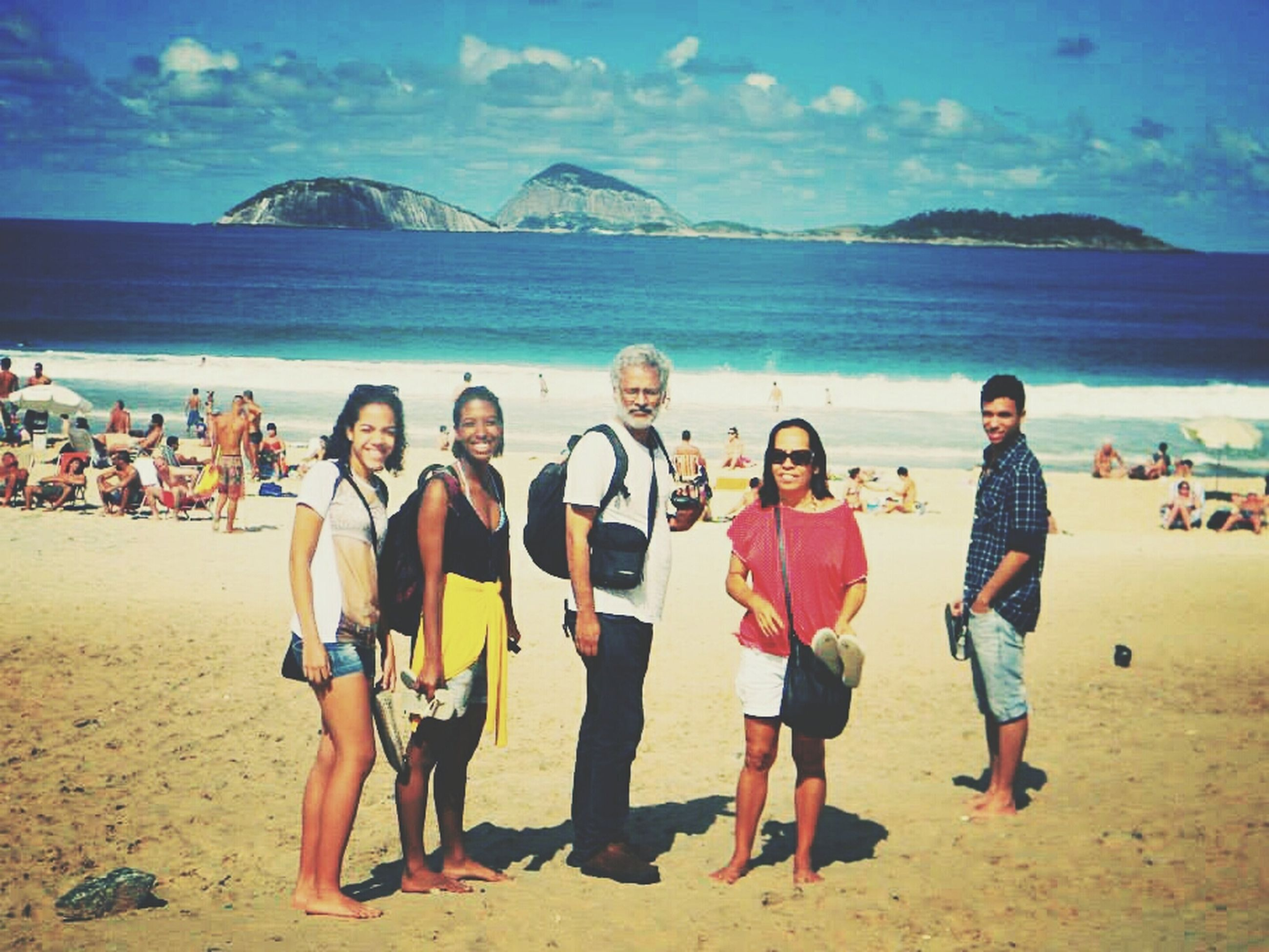 beach, lifestyles, sea, leisure activity, water, vacations, sand, togetherness, enjoyment, shore, sky, casual clothing, full length, happiness, fun, bonding, weekend activities, standing, large group of people