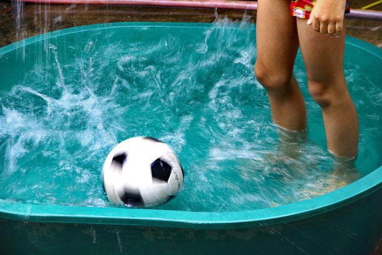 Low section of woman with soccer ball standing in wading pool