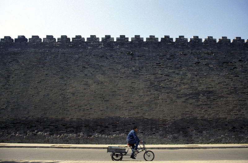 Man Riding Cart With Fortified Wall In Background