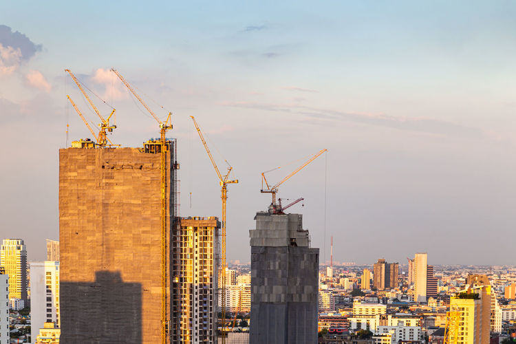 High rise building under construction, construction crane and modern city.