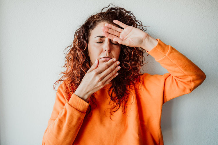 Sick woman with eyes closed standing against wall