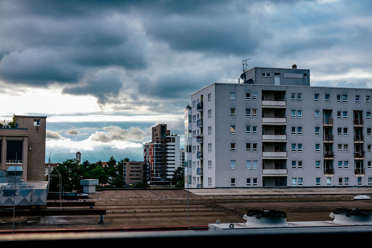 Exterior Of Buildings Against Cloudy Sky In City