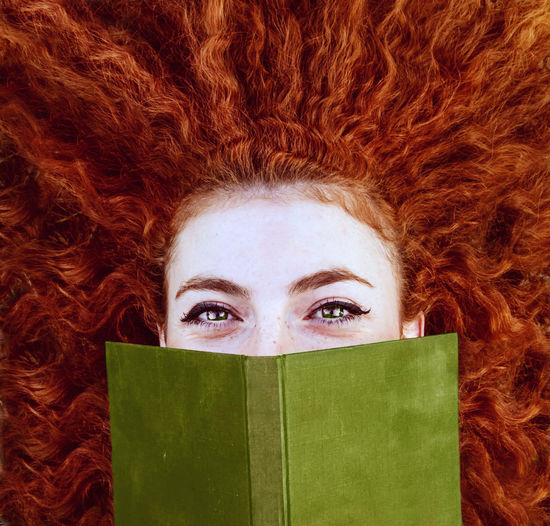 Directly Above Shot Of Redhead Woman Holding Book While Lying On Field