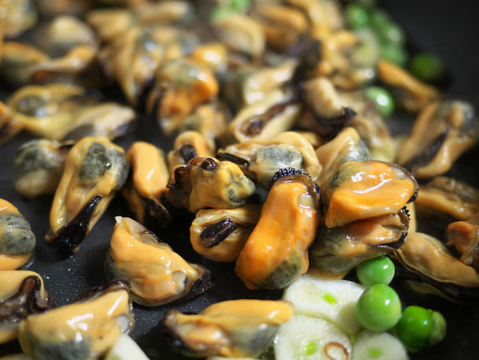 Close-Up Of Mussels And Green Peas In Frying Pan