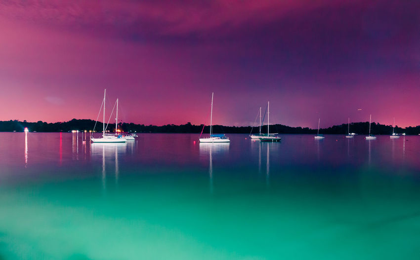 Sailboats Moored On Sea Against Sky At Night