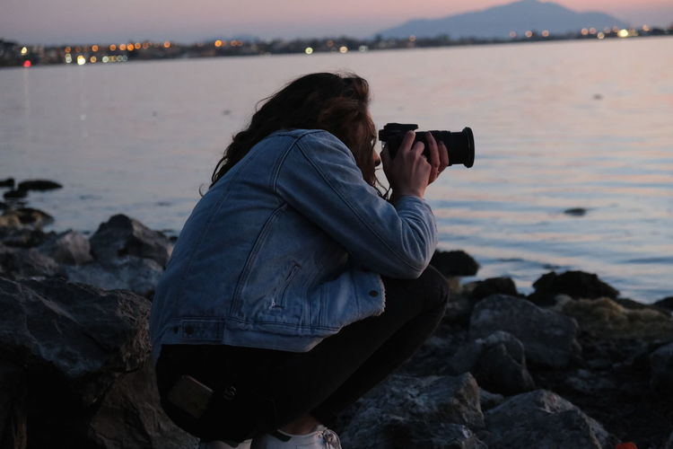 Midsection of woman photographing on rock at beach