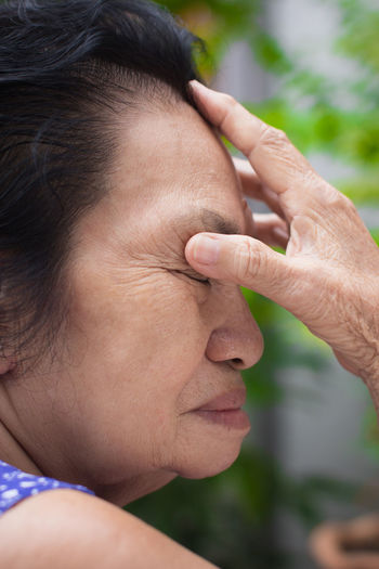 Side View Of Woman Suffering From Headache