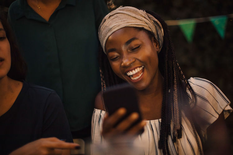 Young woman laughing while looking at mobile phone during dinner party with friends in backyard