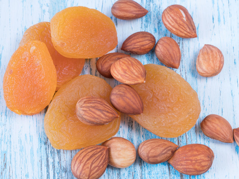 Heap of dried apricots and kernel on wooden background Apricot Apricots Blue Food Kernel Wood Wooden
