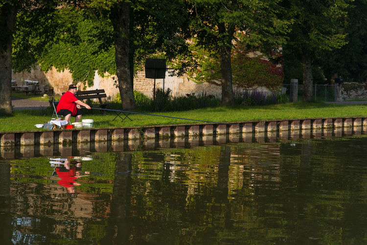 Reflection of boy in puddle on lake during rainy season