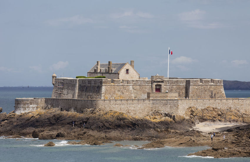 Fort with tourists on tidal island Petit Be in Saint-Malo, France. The fort was built in 17th century. It was part of the defense belt designed by Vauban. Architecture Atlantic Ocean Bretagne Building Exterior Castle Cliff Flag Fort Fortified Wall Fortress France Island Military Old Buildings Old Ruin Patriotism People Petit Bè Saint-Malo Sea Stone Wall Surrounding Wall Tidal Island Travel Destinations Vauban