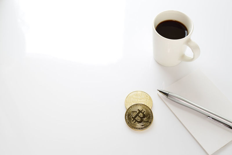 High Angle View Of Coffee Cup With Bitcoins On White Background