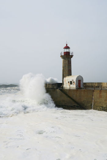 lighthouse farol das felgueiras and big waves of the atlantic ocean in porto, portugal Lighthouse Coastline White Water Atlantic Ocean Clear Sky Sea Water Lighthouse Beach Wave Motion RISK Power In Nature Sky Analogue Sound