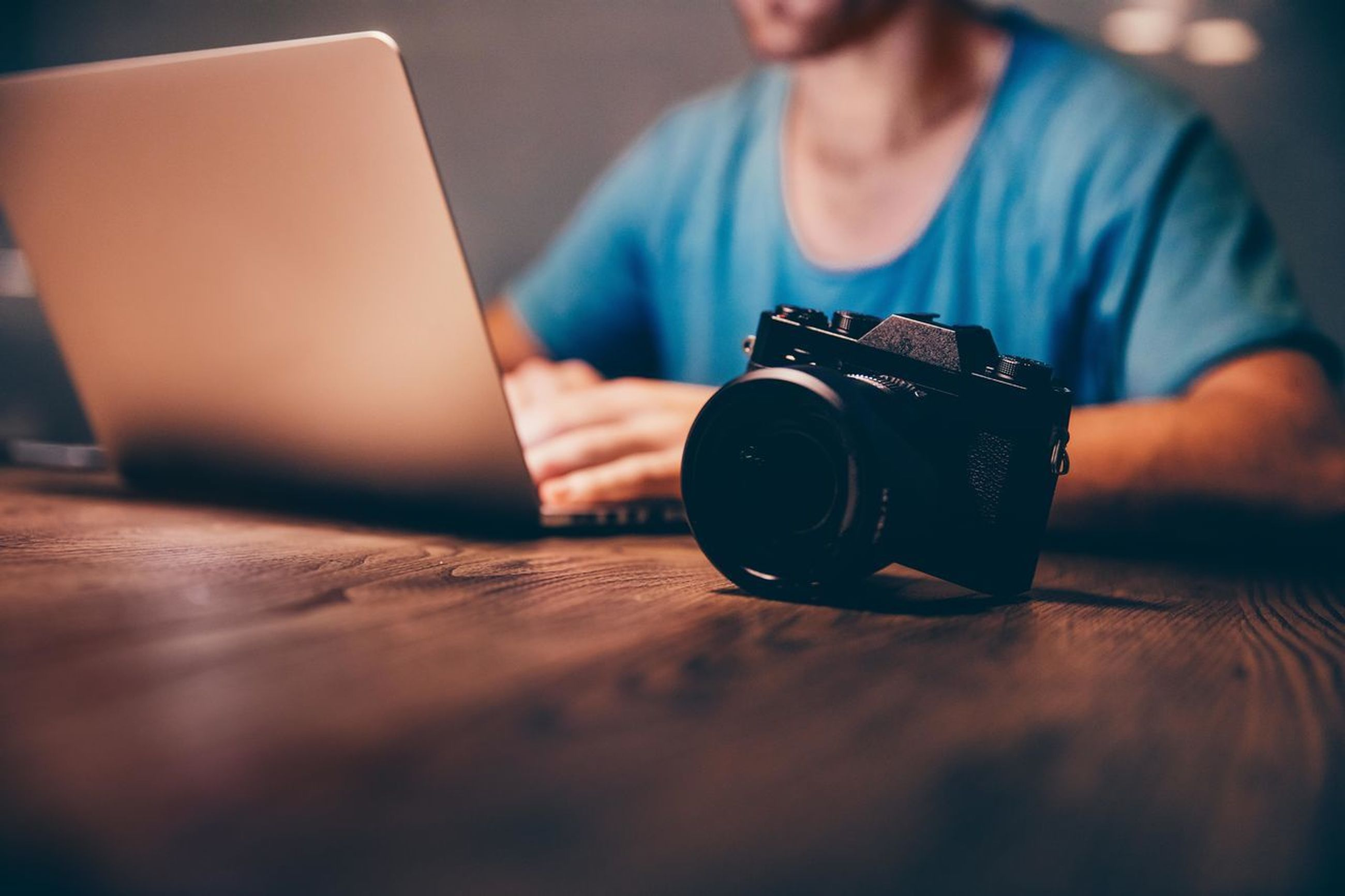technology, photography themes, camera - photographic equipment, using laptop, wireless technology, laptop, one person, real people, table, communication, men, photographic equipment, holding, selective focus, indoors, connection, occupation, computer, activity, photographer, digital camera, modern