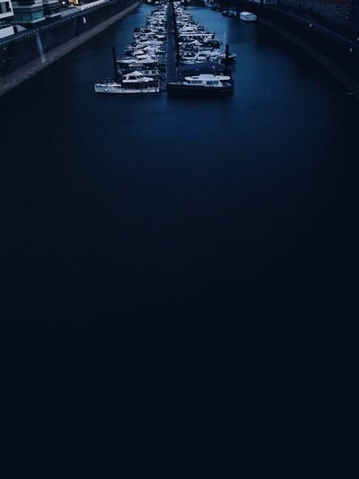High angle view of boats moored in row on river at dusk