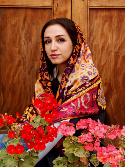 Portrait of woman in headscarf with flowers against wood