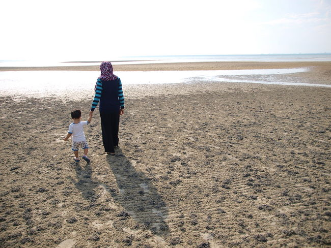 A mother walk with her child at the beach Beach Evening Walk Horizon Over Water Malaysia Mother And Son Mother's Love Port Dickson Malaysia Silhouette Toddler  Walking By The Beach
