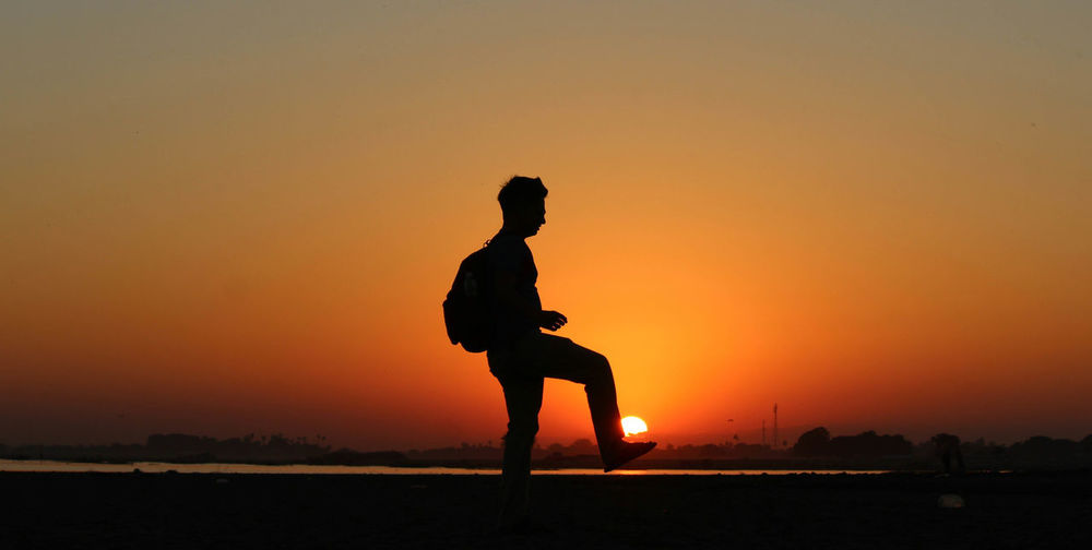 Side view of silhouette man standing against orange sky