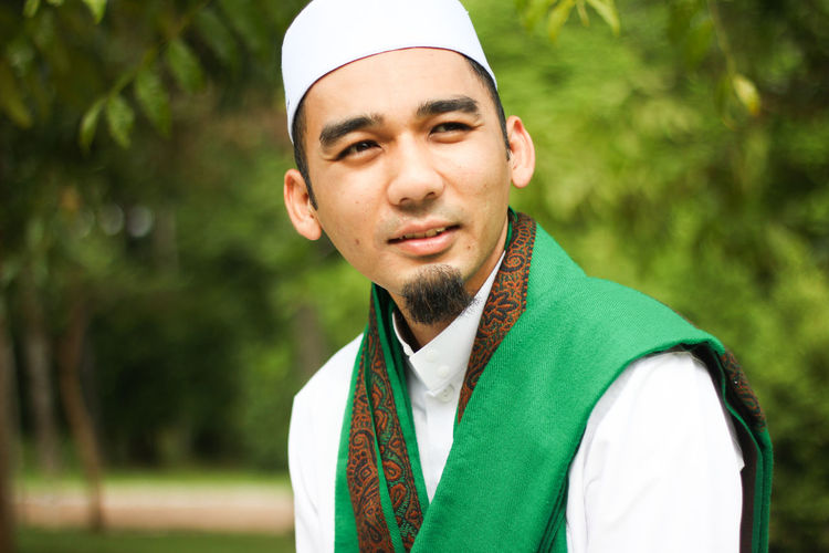 Smiling Muslim Man holding in closeup shot Adult Adults Only Beard Casual Clothing Close-up Day Focus On Foreground Green Color Headshot Human Islam Islamic Muslim Nature One Man Only One Person Only Men Outdoors People Portrait Real People Smile Standing Tree Young Adult