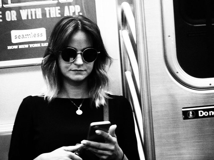 Portrait of mature woman using mobile phone in bus