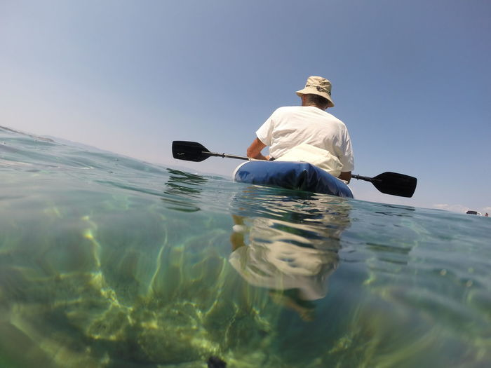 Rear view of man kayaking in sea against sky