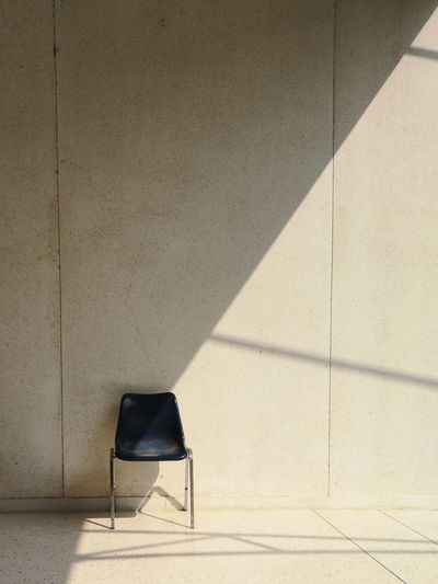 Shadow of chair on tiled floor against wall