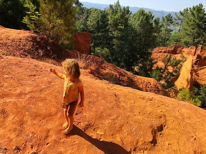 Girl standing on rock formation during sunny day