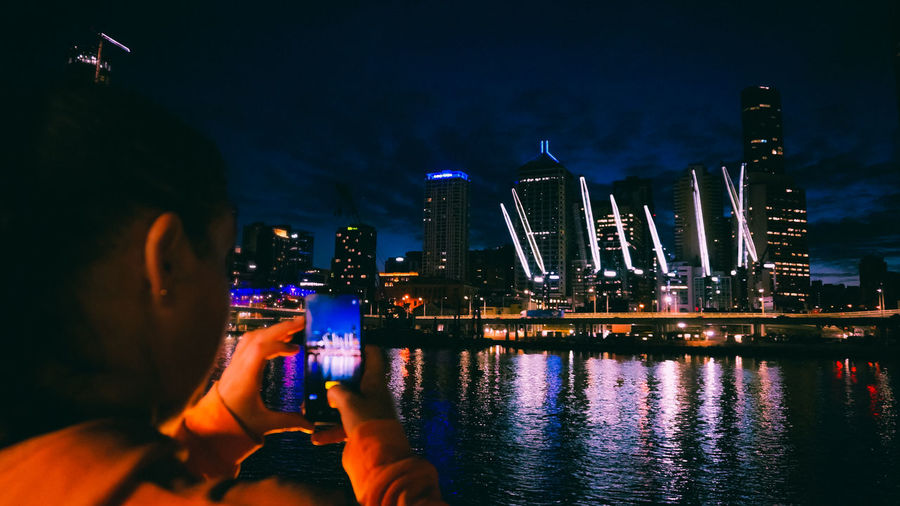 People photographing illuminated modern buildings in city at night
