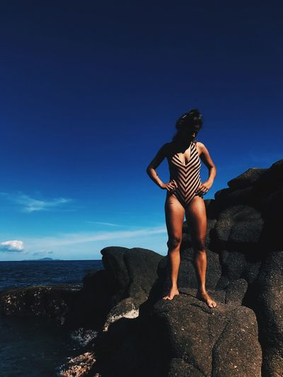 Woman wearing swimsuit while standing on rock against blue sky