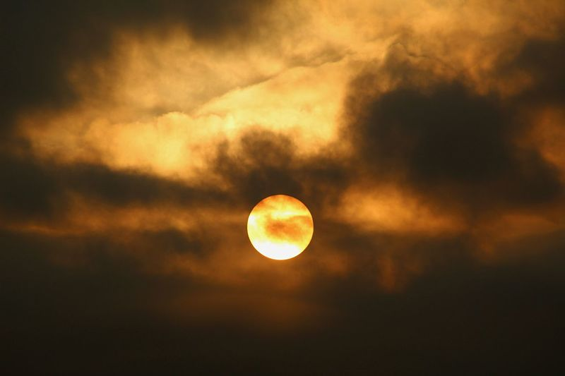 Low angle view of sun in cloudy sky during sunset