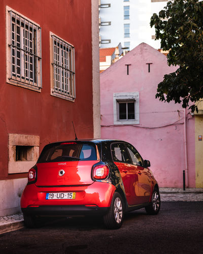 Red toy car on street against buildings in city