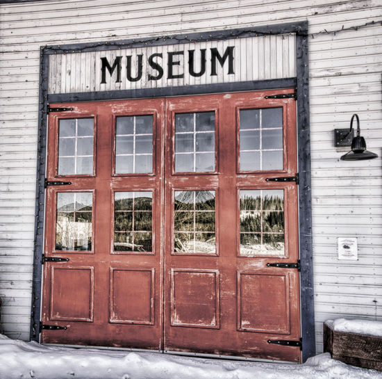 Old Museum Garage Door Architecture Reflection Old Door Museum Window Outdoors Canada Weathered Rustic Antique Old Buildings Historic Red Door Dawson City  Hinges Garage Door Weathered Wood Building Exterior Built Structure Wood - Material Building Exteriors Yukon Territory Text Day No People Close-up