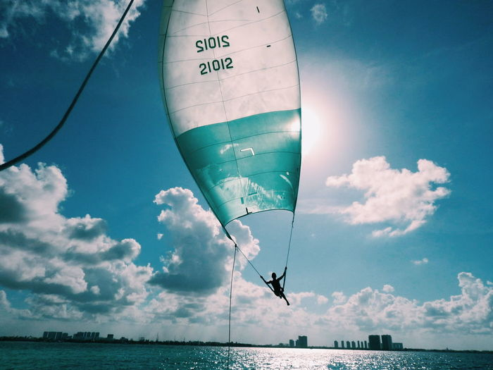 Silhouette of person parasailing over sea against cloudy sky
