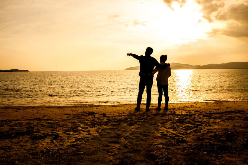 silhouette of people at the beach,The beauty of natural light at sunset. Sunset Sky Water Sea Beach Land Two People Real People Scenics - Nature Beauty In Nature Silhouette Standing Togetherness Horizon Over Water Leisure Activity Horizon Nature Men Positive Emotion Couple - Relationship Sun Outdoors Human Arm Silhouette Happiness Happy People Holiday Relaxing Children Women Man Romantic Orange Clouds And Sky Love Family Summer Sunrise Boy Freshair Freedom Fun