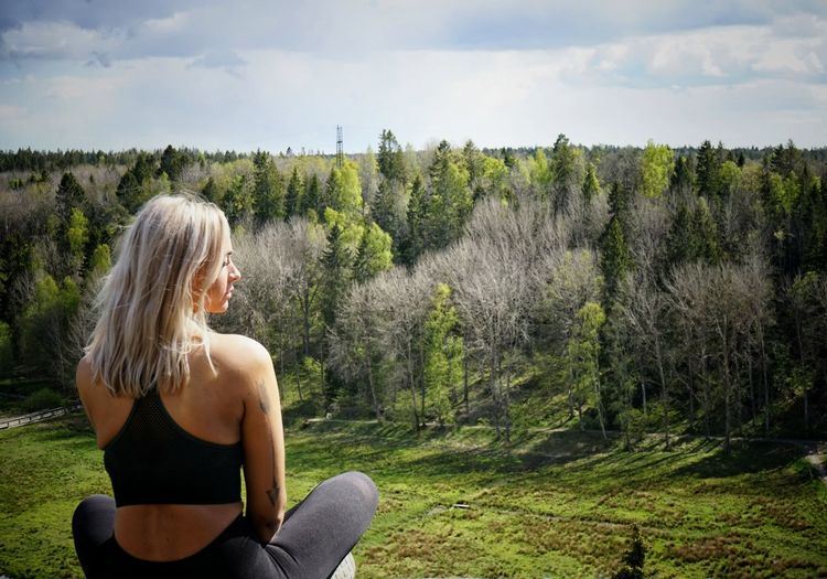 Beautiful woman sitting on land against trees