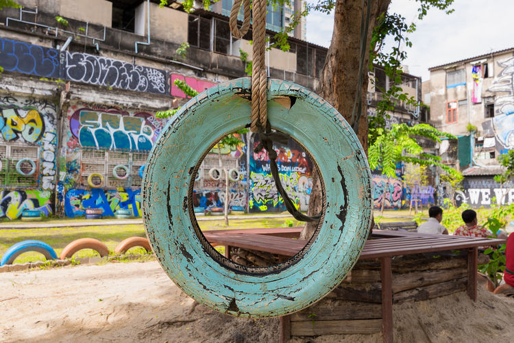 A old style tyre swing in a city children's play park with old cracking paint hanging from a tree by a thick rope. City Park Public Park Architecture Art And Craft Building Exterior Built Structure Close-up Day Graffiti No People Old Paint Old Tyre Outdoors Park Play Area Rope Swing Swing Tree Tyre Swing