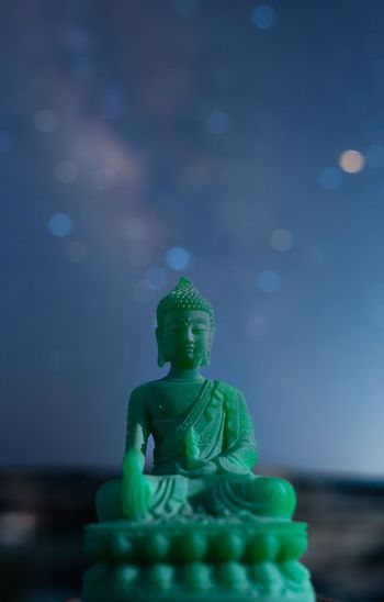 Close-up of buddha statue against sky