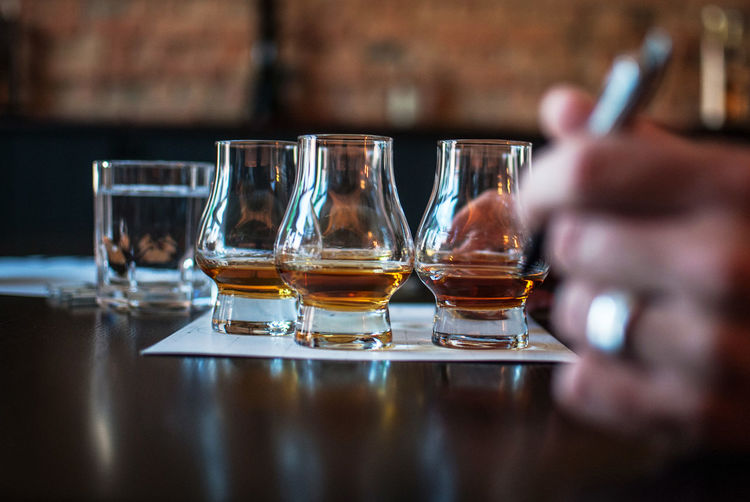 Close-up of hand holding pen against scotch whiskey in glasses at table